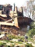 Камни местных жителей против бульдозера, разрушающего могилы