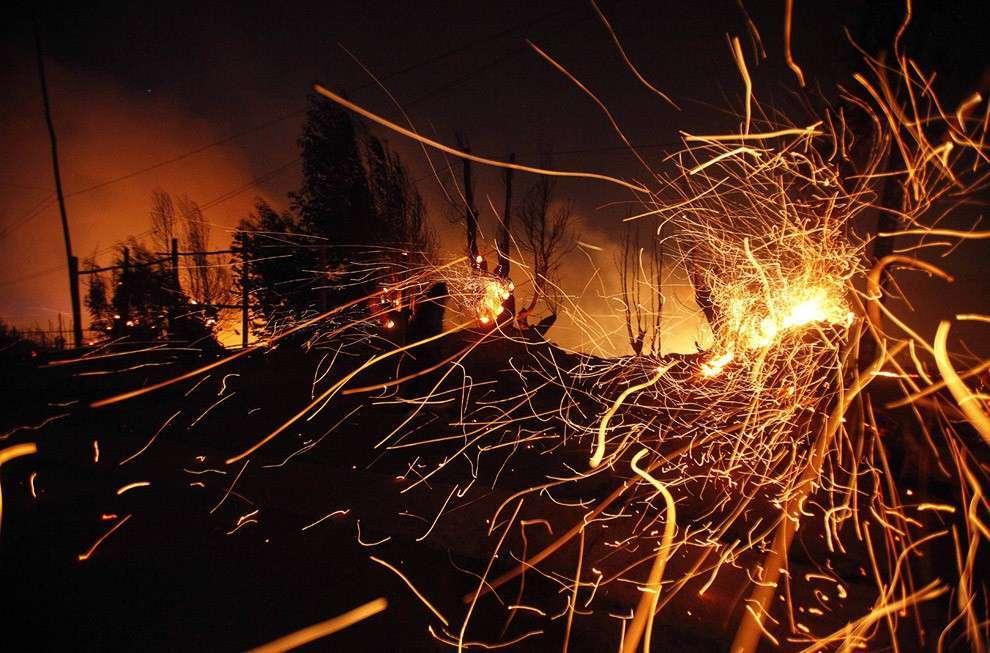 Тлеющие угли на остатках сгоревшего дома