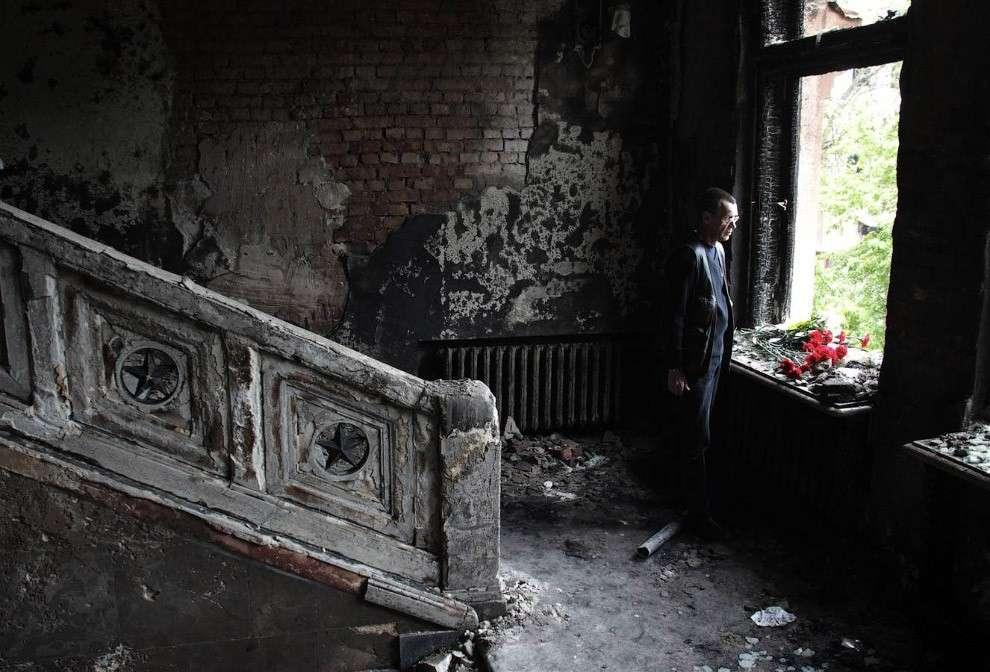 Человек с цветами в обгоревшем здании Дома профсоюзов в Одессе