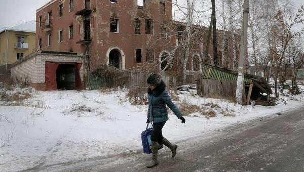 Женщина проходит мимо разрушенного дома в Семеновке, Донецкая область, Украина