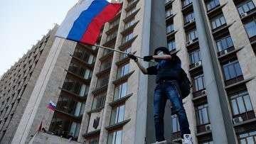 Активист с российским флагом у здания областной администрации в Донецке