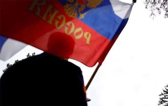 На параде в честь независимости Эстонии в Нарве местный житель приветствовал натовских военных флагом России и гимном СССР. Мужчина с флагом России