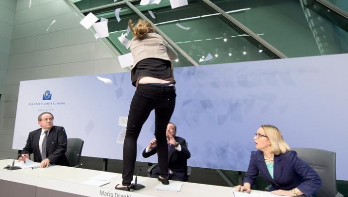 Девушка запрыгнула на стол главы ЕЦБ и обсыпала его бумажками