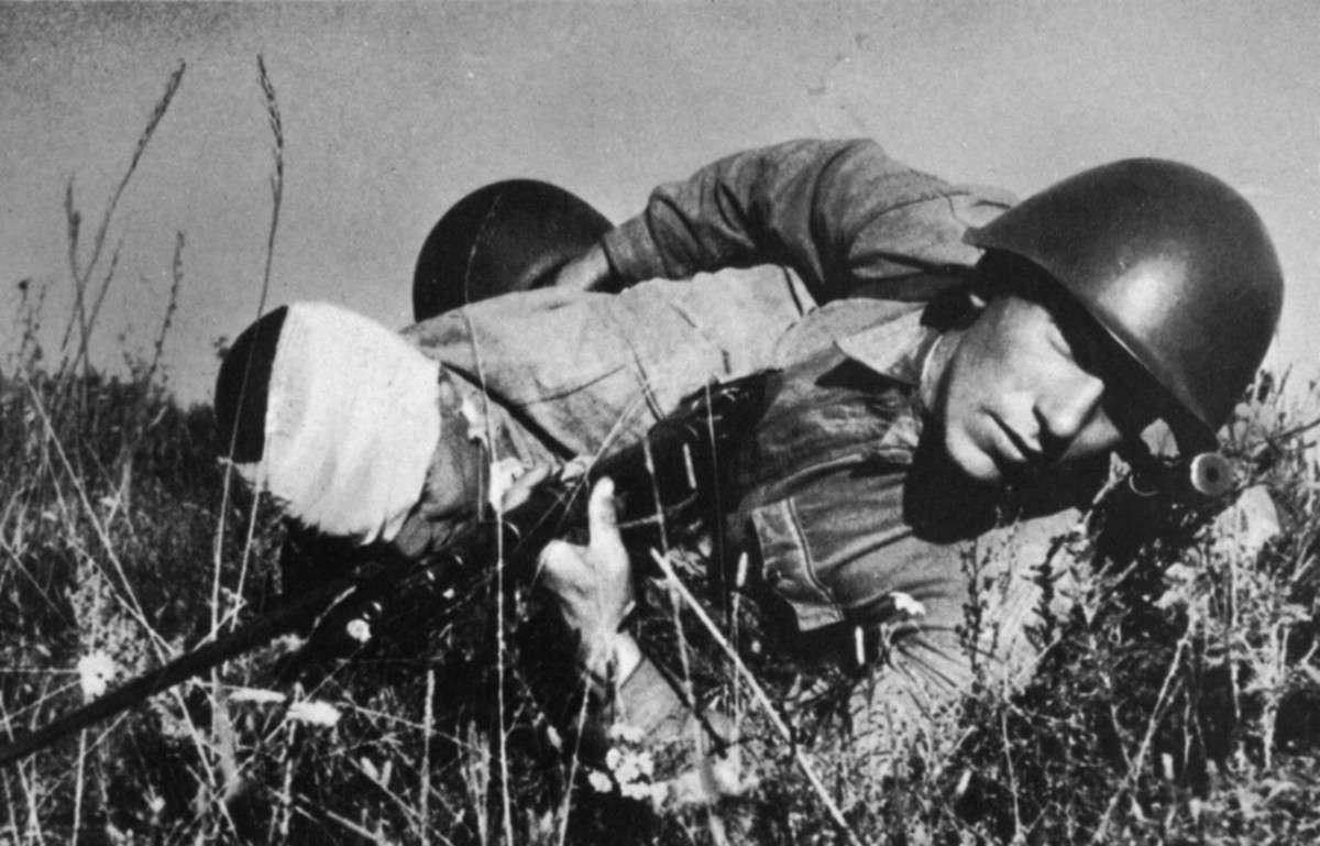 Красноармеец вытаскивает раненого товарища с поля боя на подступах к Сталинграду