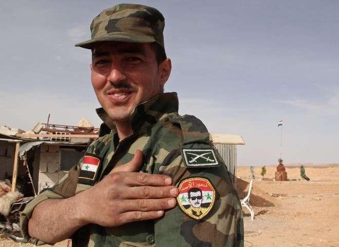 Фото: РИА/Д. Виноградов Военнослужащий сирийской армии демонстрирует нашивку с портретом Башара Асада