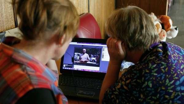 Беженцы из Украины смотрят новости в Интернете. Архивное фото