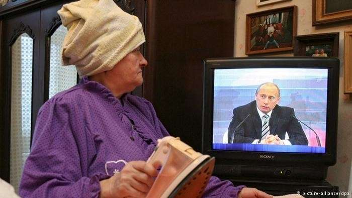 злорадно ухмыляющийся Путин в телевизоре