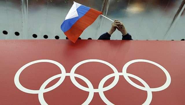 Болельщик держит российский флаг над логотипом олимпийских игр. Архивное фото