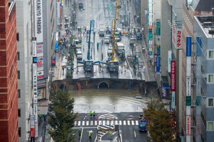 Провал грунта на городской улице города Фукуока в Японии растёт