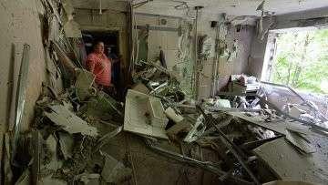 Жители многоквартирного дома на окраине Донецка, пострадавшего от артиллерийского обстрела города украинскими силовиками, в своей разрушенной квартире.