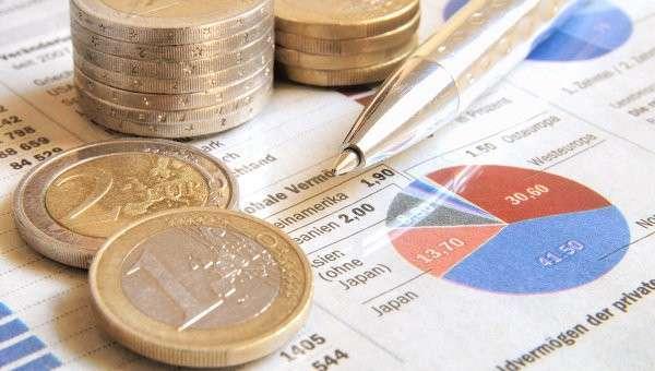 Монеты стоимостью 1 и 2 евро на бумагах с биржевыми сводками. Архивное фото