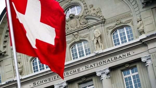 Флаг Швейцарии на фоне здания Национального Швейцарского банка, Берн. Архивное фото.