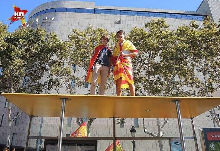 Мальчишки забрались на автобусную остановку с флагами Испании Фото: Дарья АСЛАМОВА