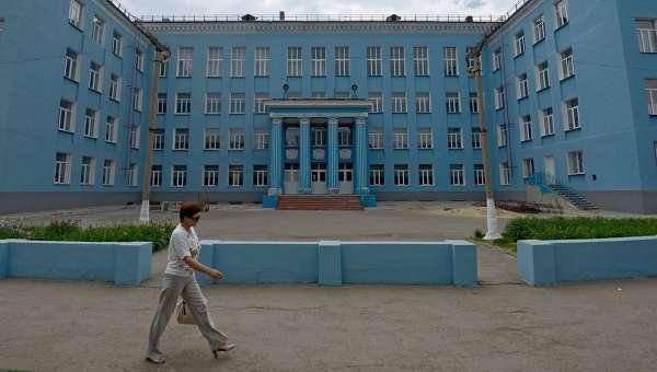 Прохожая у здания школы в Луганске. Архивное фото