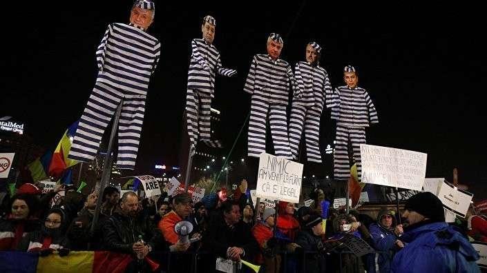 Митингующие держат чучела с лицами лидеров левых социал-демократов Румынии, одетых как узники, во время протестов в Бухаресте