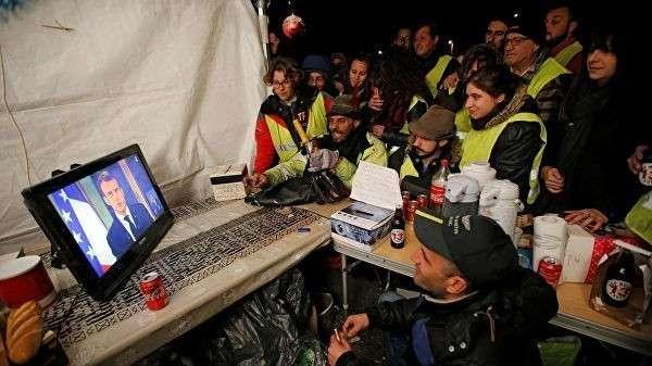 Протестующие в желтых жилетах смотрят выступление президента Франции Эммануэля Макрона неподалеку от Марселя