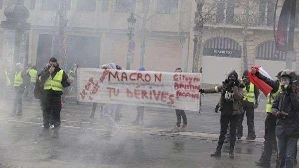 Участники акции протеста движения желтых жилетов в Париже.