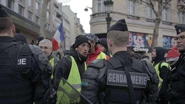 Сотрудники полиции и участники акции протеста движения автомобилистов желтые жилеты в районе Триумфальной арки в Париже. 15 декабря 2018