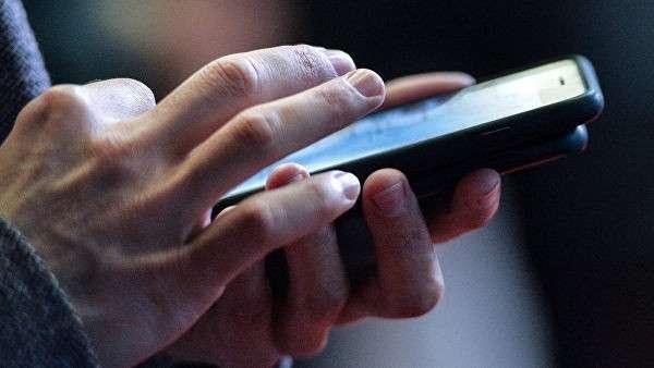 Молодой человек с телефоном в руках. Архивное фото