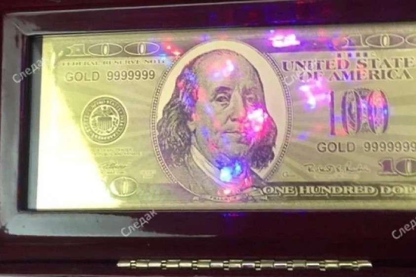 Эта 100-долларовая купюра сделана из чистого золота. Фото: оперативная съёмка