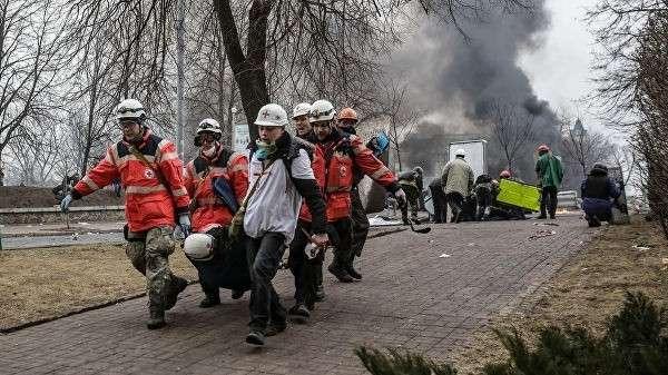 Сторонники оппозиции несут раненного за баррикады на площади Независимости в Киеве
