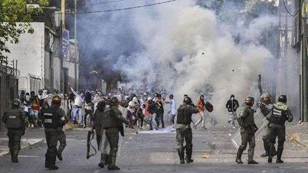 Столкновения полиции с демонстрантами во время акции протеста против правительства Николаса Мадуро в Каракасе. 23 января 2019
