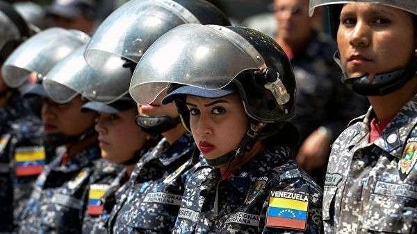 Члены Боливарианской национальной полиции во время акции против политики президента Венесуэлы Николаса Мадуро в Каракасе