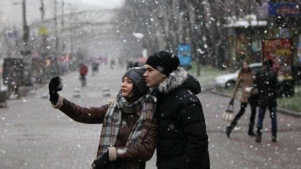Молодые люди во время снегопада в Киеве