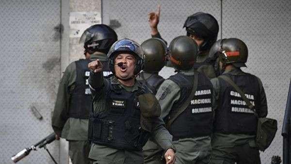 Члены Национальной гвардии Венесуэлы во время стычек с протестующими в Каракасе. 21 января 2019