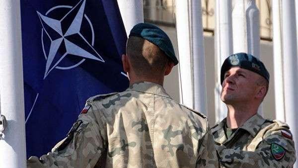 Военнослужащие поднимают флаг НАТО