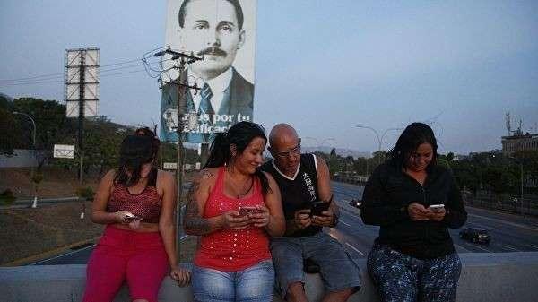 Люди пытаются поймать сигнал мобильной связи на хайвее в Каракасе