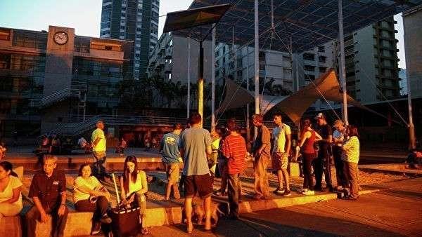 Люди выстроились в очередь к аккумулятору с солнечной панелью на площади в Каракасе, чтобы зарядить телефоны