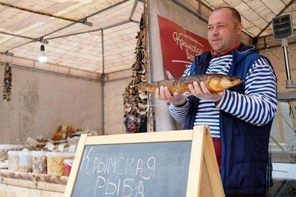 Продавец демонстрирует рыбу для продажи на ярмарке в рамках фестиваля Крымская весна в Краснодаре