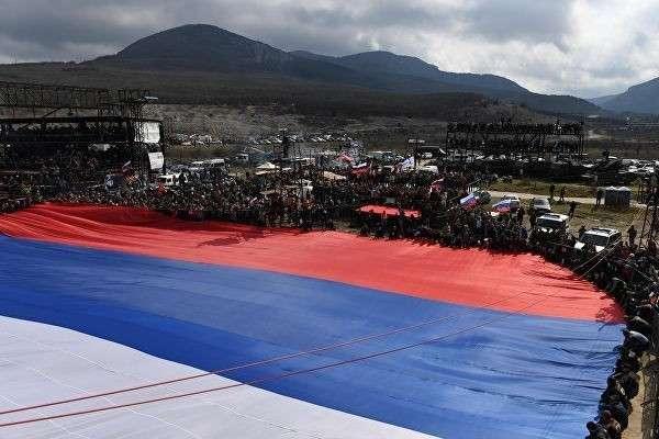 Участники автопробега, организованного мотоклубом Ночные волки, растягивают гигантский флаг России на горе Гасфорта в Севастополе
