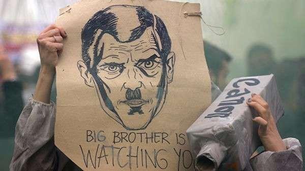 Участница акции протеста с плакатом Большой Брат следит за тобой
