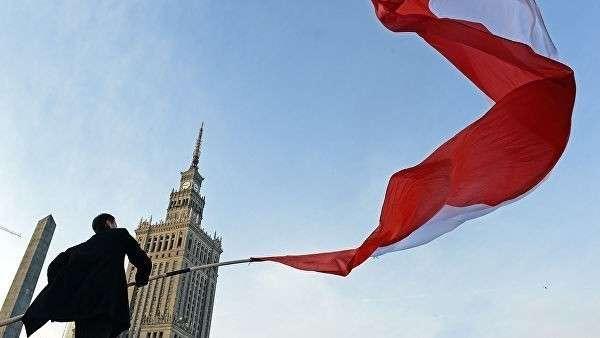 Мужчина держит польский флаг