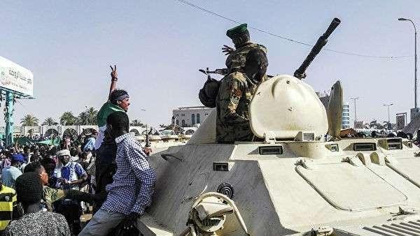 Протестующие против президента страны Омара аль-Башира приветствуют военных у комплекса зданий Министерства обороны в Хартуме, Судан. 9 апреля 2019