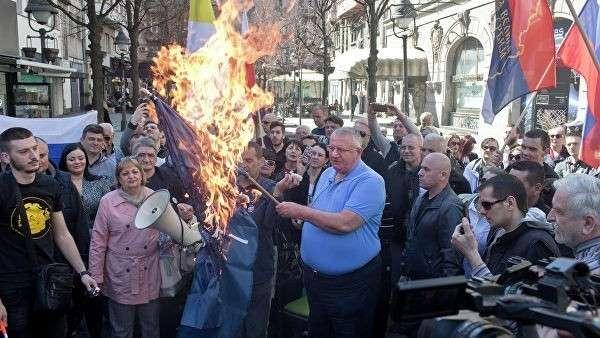 Воислав Сесель, лидер ультранационалистической сербской радикальной партии, держит горящий флаг НАТО на акции протеста в Белграде, Сербия