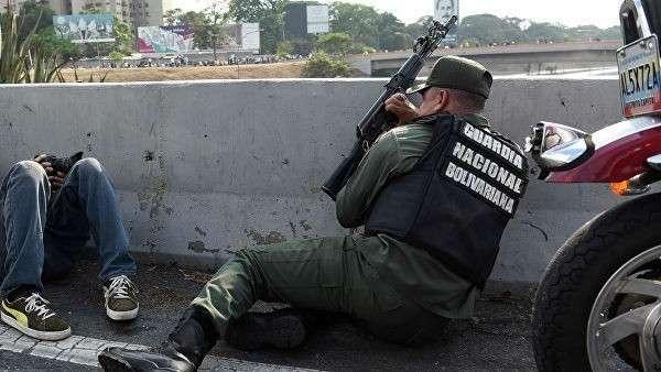 Сотрудник Национальной гвардии Венесуэлы, поддерживающий оппозиционного лидера Хуана Гуаидо, на шоссе Франсиско Фахардо