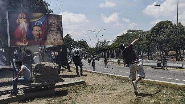 Сторонник оппозиции кидает коктейль Молотова во время столкновения с Национальной гвардией Венесуэлы в районе аэропорта Каракаса