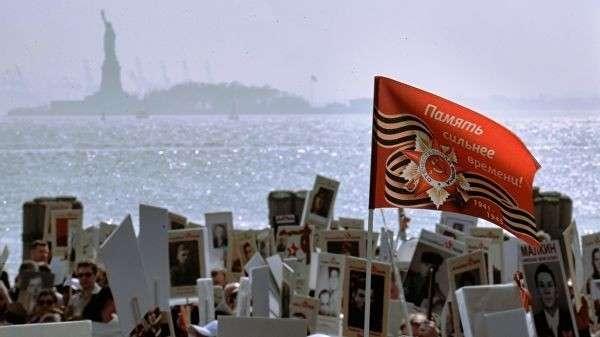 Транспаранты и флаг в руках участников акции Бессмертный полк в Нью-Йорке