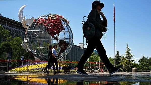 Люди проходят мимо глобуса с изображением США у банка в Пекине