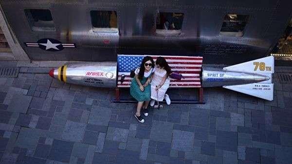 Девушки делают селфи сидя на скамейке с флагом США возле магазина в Пекине. 3 мая 2018 года