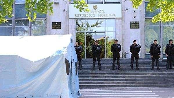 Сотрудники правоохранительных органов охраняют вход в здание правительства Молдавии во время митинга сторонников Демократической партии Молдавии