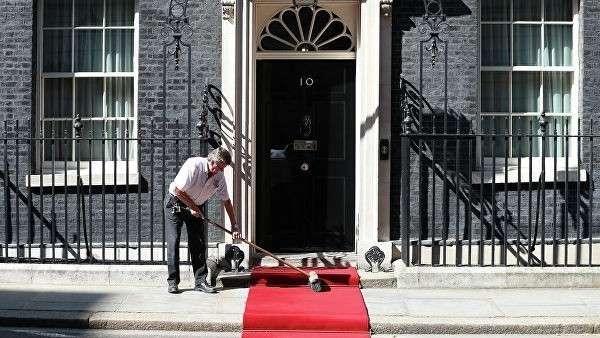Рабочий подметает красную ковровую дорожку на Даунинг-стрит, 10 в Лондоне