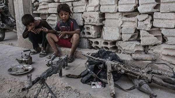 Дети смотрят на оружие, оставленное боевиками ИГ (запрещена в РФ) в Кобани, Сирия. 2015 год.