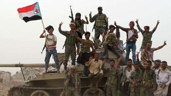 Члены поддерживаемых ОАЭ южно-йеменских сепаратистских сил стоят на танке во время столкновений с правительственными войсками в Адене, Йемен. 10 августа 2019