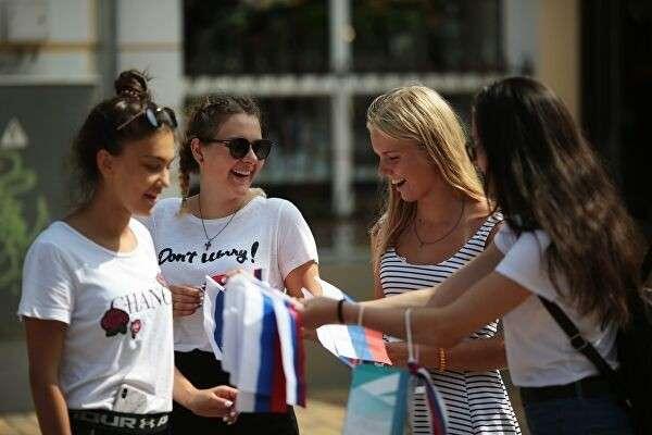 Девушки раздают прохожим флаги в рамках празднования Дня государственного флага Российской Федерации в центре Симферополя