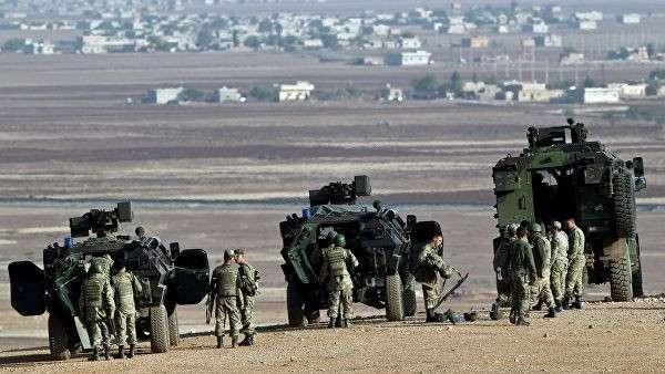 Турецкие солдаты стоят на холме с видом на сирийский город Кобани, недалеко от Сурука, на границе между Турцией и Сирией