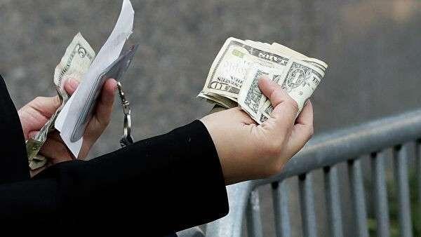 Женщина расплачивается наличными в Нью-Йорке